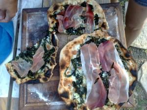 Fette di speck sopra la pizza appena sfornata