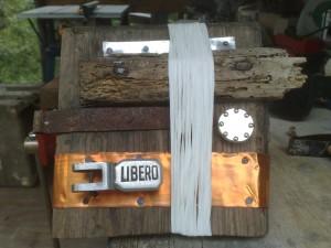 'Libero' - scultura in legno, alluminio, rame, spago in cellulosa, il fermo di una finestra di tram milanese (trovato per terra)